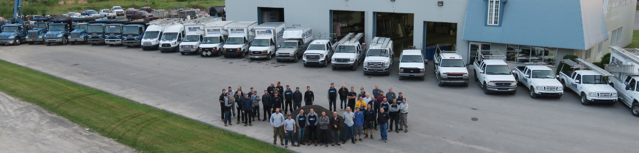 Équipe de couvreurs de bellemare couvertures devant 23 camions